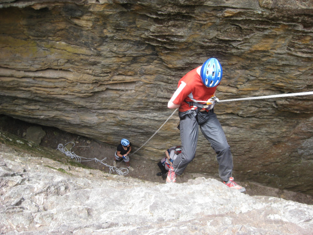 An only too common sight: the belayer is holding her hands low, not looking at the abseiler and talking to a bystander instead. She would hardly be able to stop the abseiler in time if anything were to happen.
