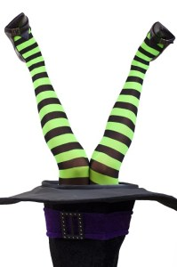 Witch's legs sticking out of a black top hat. Hat and legs are upside down. Green and black striped tights.