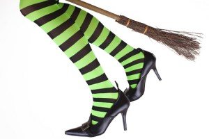 Witches legs running with broom.  Green and black striped tights.