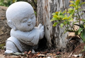 Cement child budha in robe pushing against a tree trunk in a garden. Tranquil
