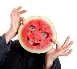Person holding a round slice of watermelon in front of their face. A smiley face has been cut out and the person's eyes and mouth show through the holes