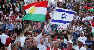 A Kurdish man holds an Israeli and Kurdish flag during a rally to show their support for the upcoming September 25th independence referendum in Erbil