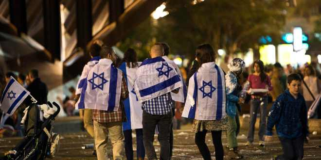 People covered with Israeli national flags walk onto Rabin square to take part in the celebrations for Israel's Independence Day at its 65th anniversary of the creation of the state in Tel Aviv