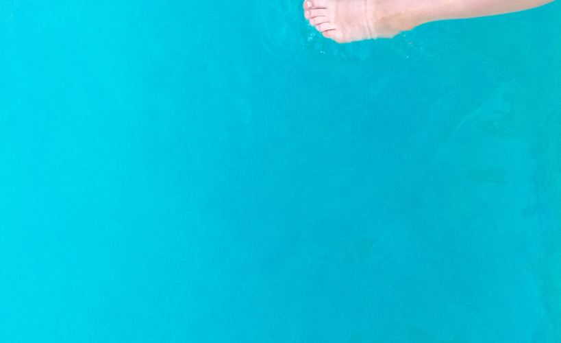 Legs in a turquoise swimming pool
