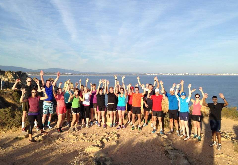 Group photo of runners cheering on the cliffs