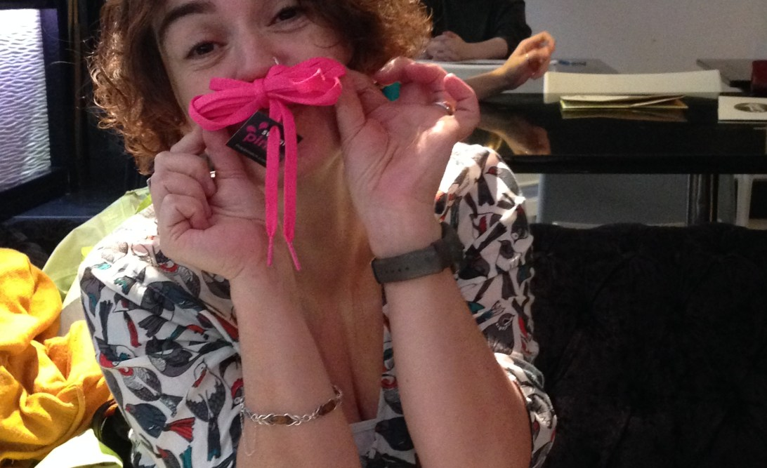 Katherine holding a pair of pink shoelaces