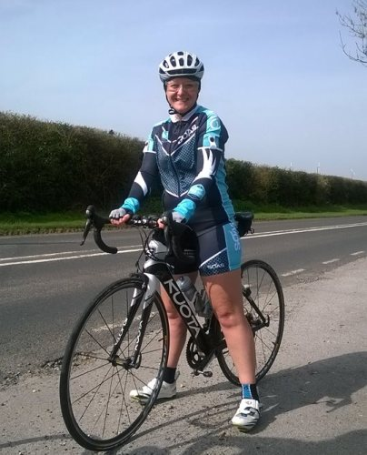 Tamsyn on her bike wearing her SOAS cycling kit