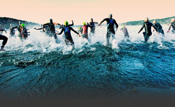 People wearing wetsuits running into the sea during an Ironman swim start