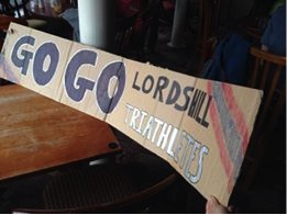 "Ellie's banner saying ""Go Go Lordshill Triathletes""."