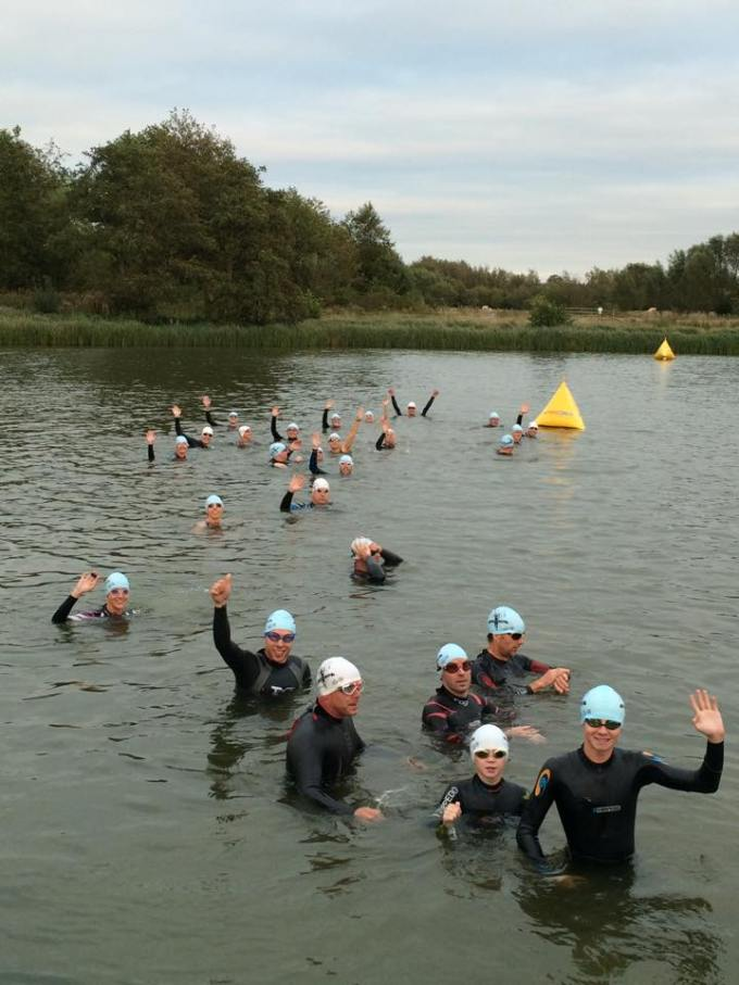 Swimmers in the lake waving.