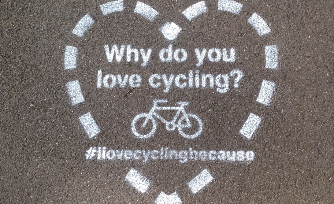Pavement stencil saying 'Why do you love cycling? #ilovecyclingbecause'