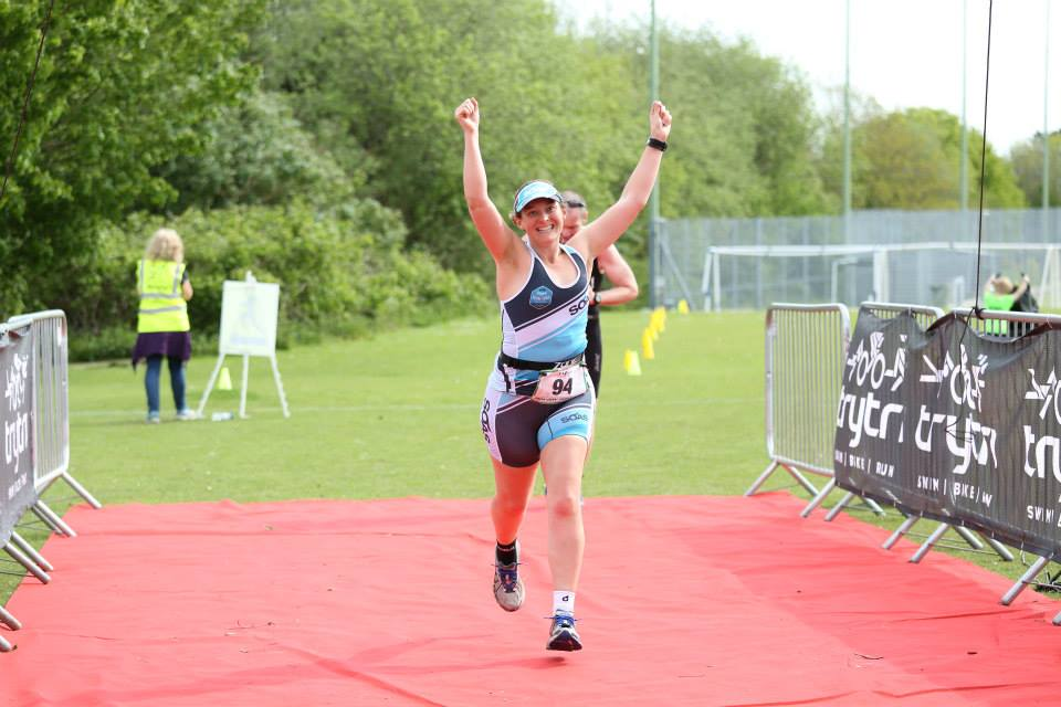 Tamsyn finishing May Day Tri with her arms aloft