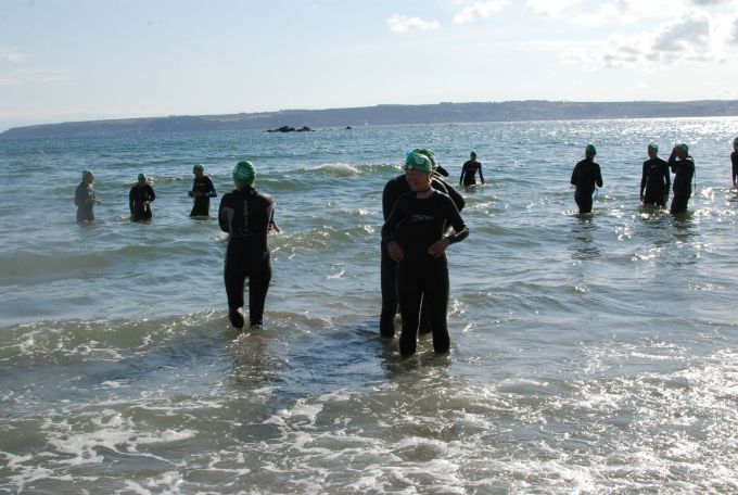 Tamsyn and Stuart standing in the water with other swimmers.