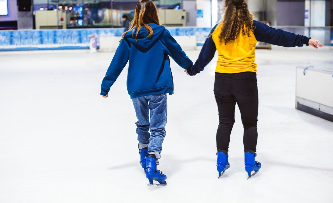 Two women ice-skating and holding hands.