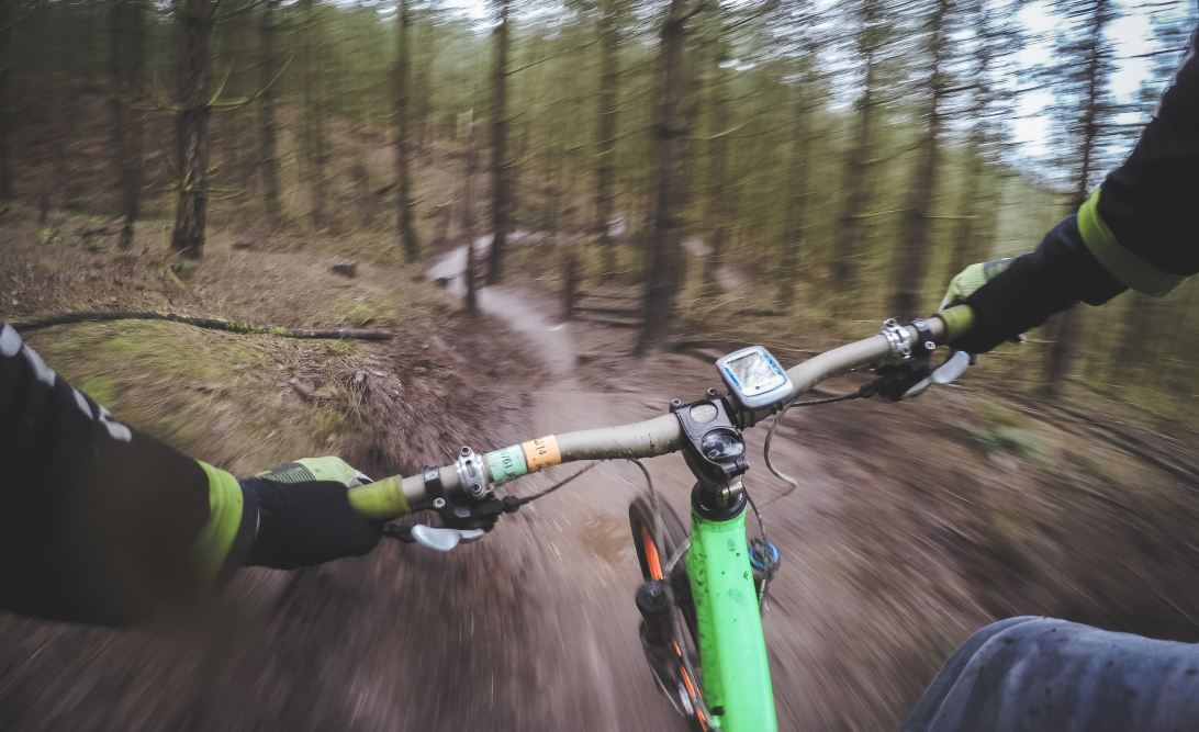 Bike handling skills illustrated by a person riding quickly downhill through a forest