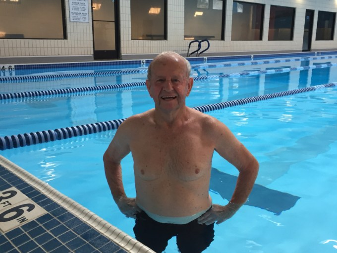A fit and healthy-looking 95-year-old swimmer standing in a swimming pool.