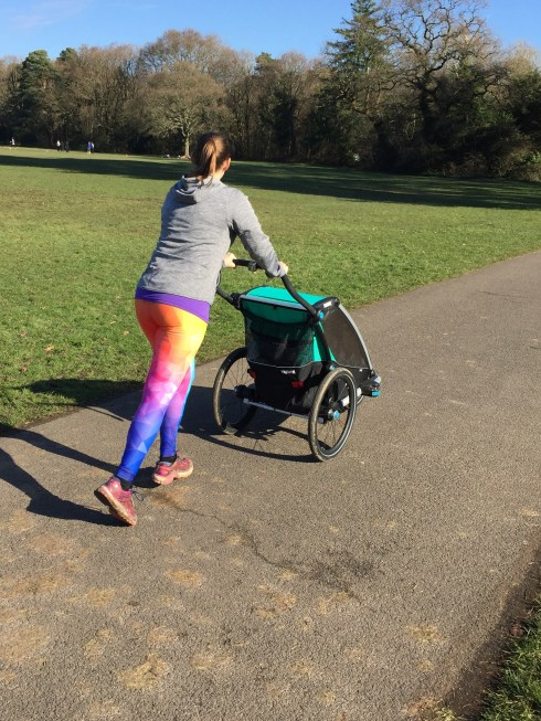 Tamsyn running and pushing a Thule Chariot Lite.