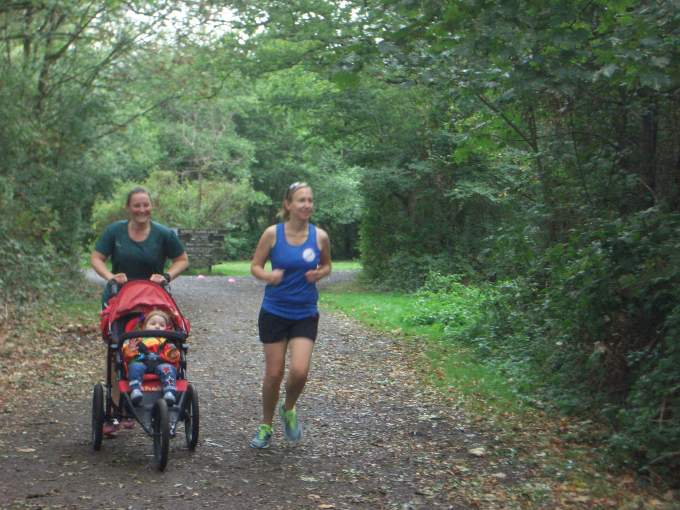 Tamsyn pushing M (and Ellie) heading to the finish funnel at Dinton Pastures parkrun