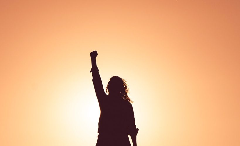 Silhouette of a person with one arm in the air.