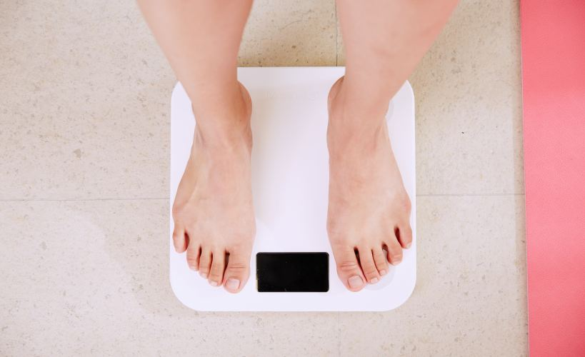 Barefeet stading on digital bathroom scales.