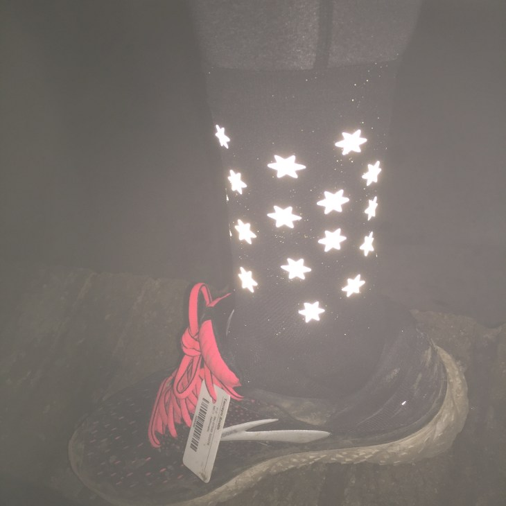 Tamsyn wearing reflective SaySky socks in the dark. The stars can be seen reflecting the light.