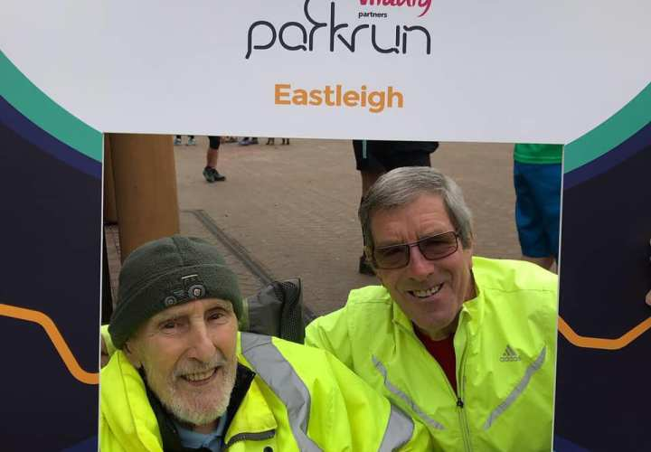 Two men in fluorescent jackets in a parkrun picture frame at Eastleigh parkrun.