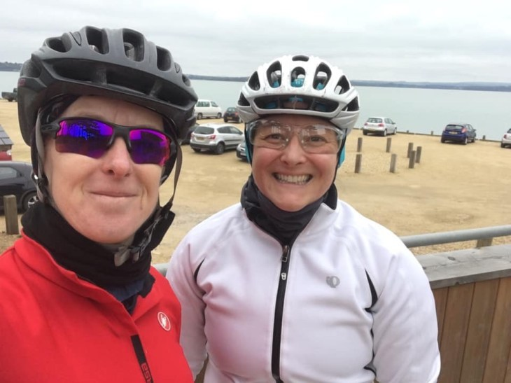 Selfie of Teri and Tamsyn in cycling kit with Lepe Beach in the background.