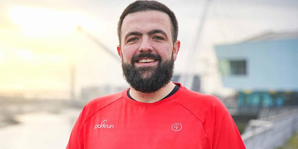 Close up of Gareth Yeoman wearing a red parkrun 50 t-shirt.
