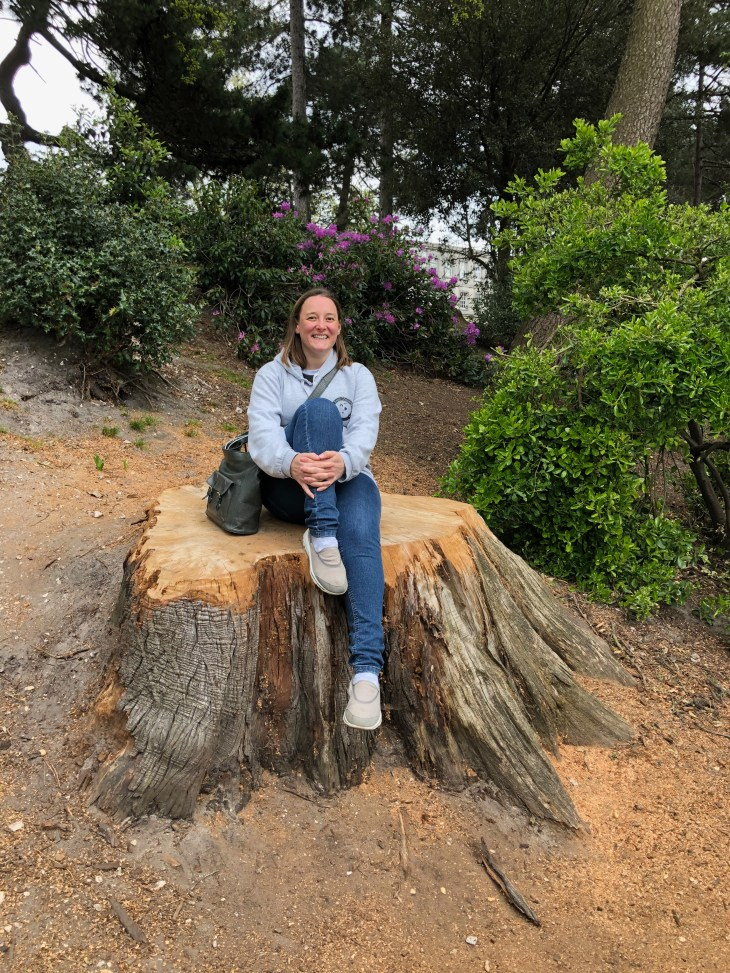 Tamsyn posing on a tree stump.