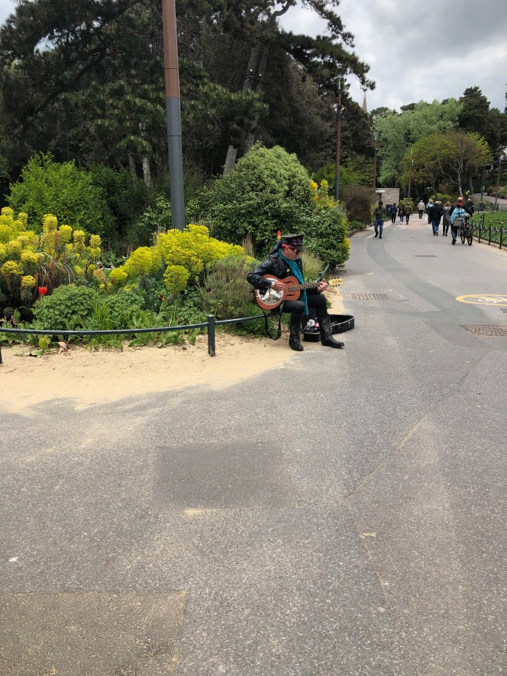 A busker in the gardens.