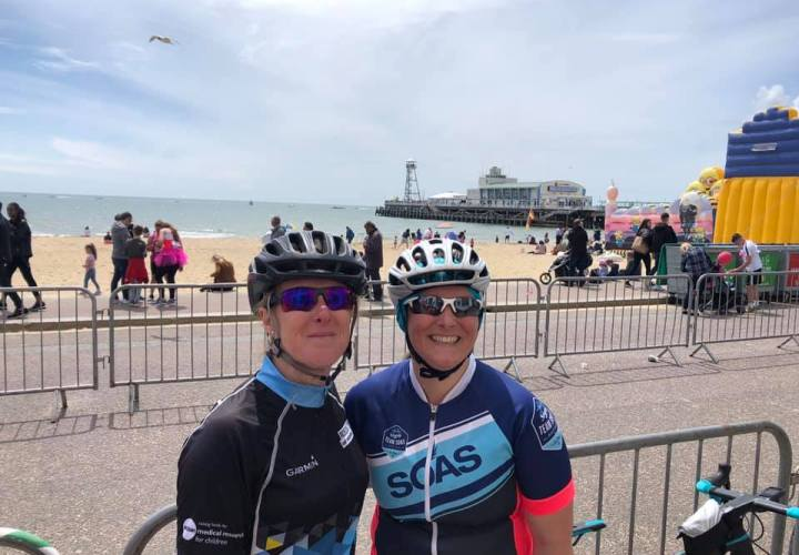 Teri and Tamsyn wearing cycling kits by the beach at Bournemouth.