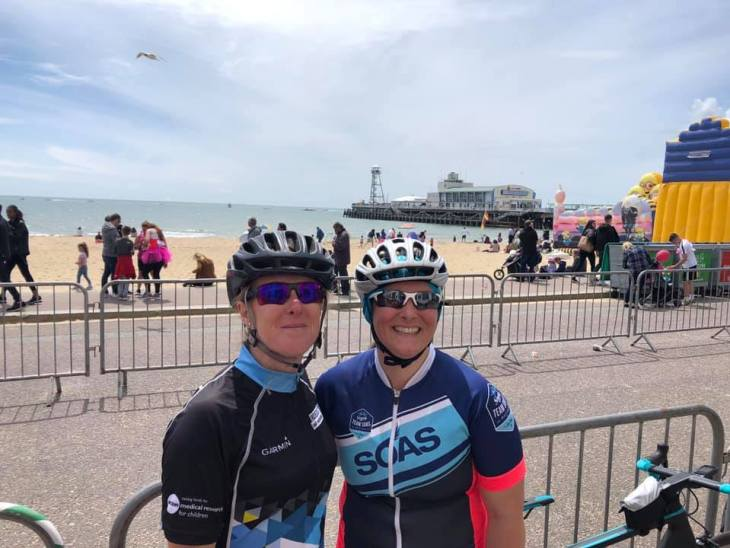 Tamsyn and Teri wearing cycling kit in front of Bournemouth pier and beach.