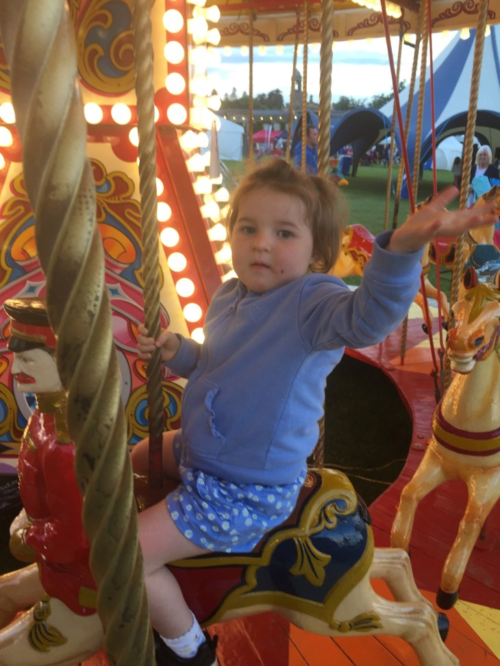 A child on a merry-go-round waving.