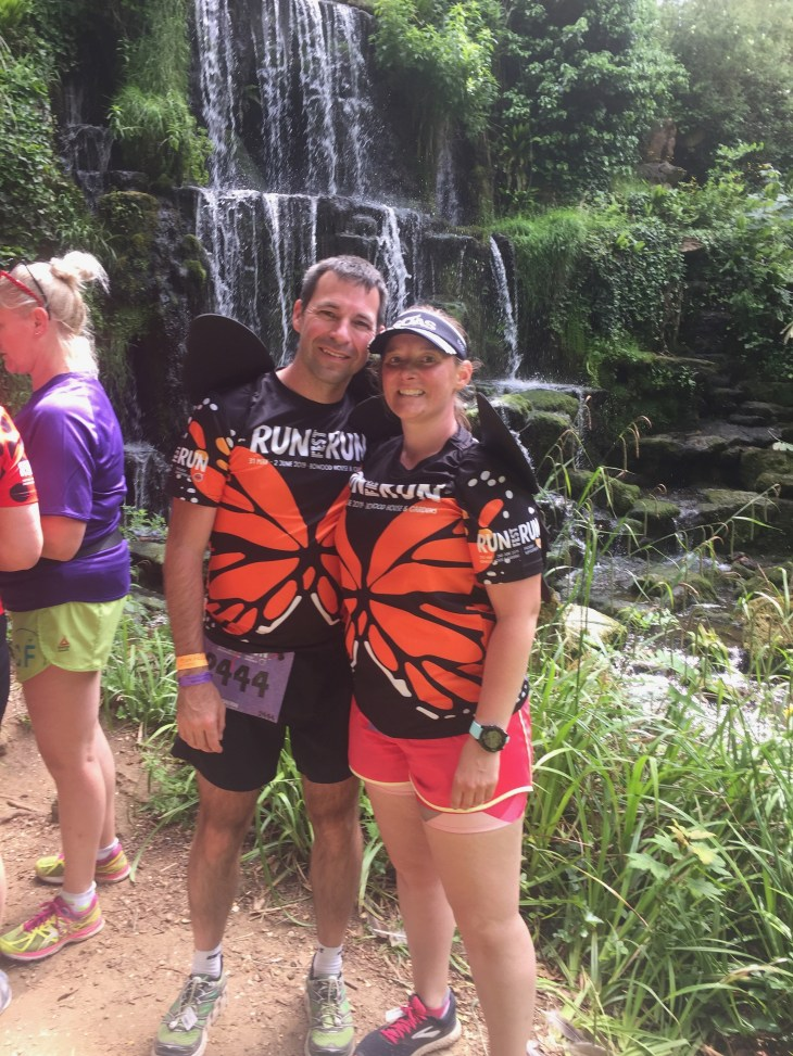 Couple wearing RunFestRun t-shirts in front of a waterfall.