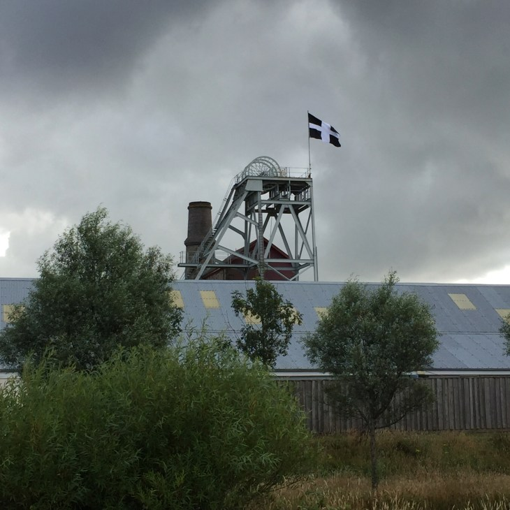Shaft head gear at Heartlands flying the flag of St Piran. The sky has grey clouds.