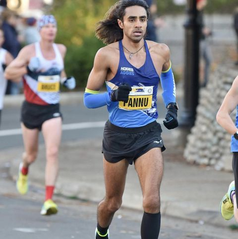 A man (Rajpaul Pannu) racing in a running singlet and shorts.