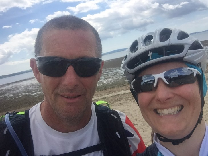 Selfie of Pete and Tamsyn by the beach at Lepe. They are wearing sunglasses and Tamsyn has on a cycling helmet.