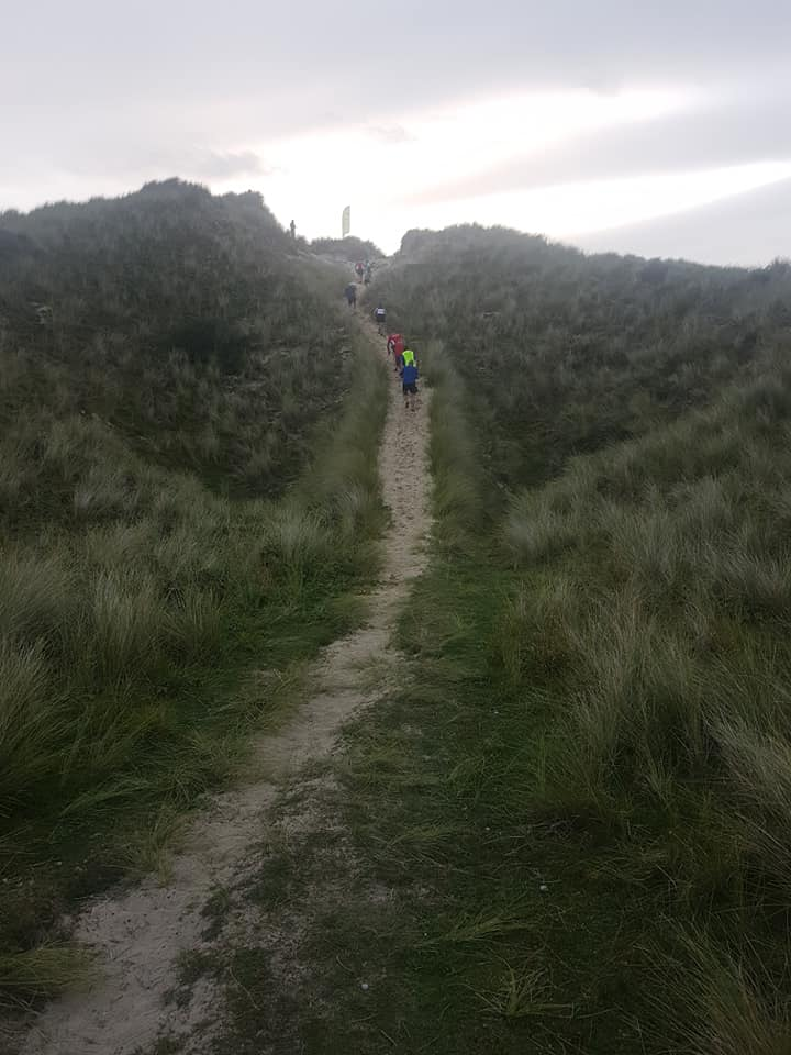 View of runners walking up a steep sand dune. Photo taken from the bottom of the slope.