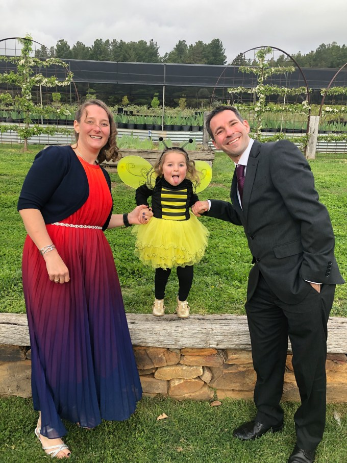 Tamsyn and Stuart wearing formal attire, with M dressed as a bumble bee.