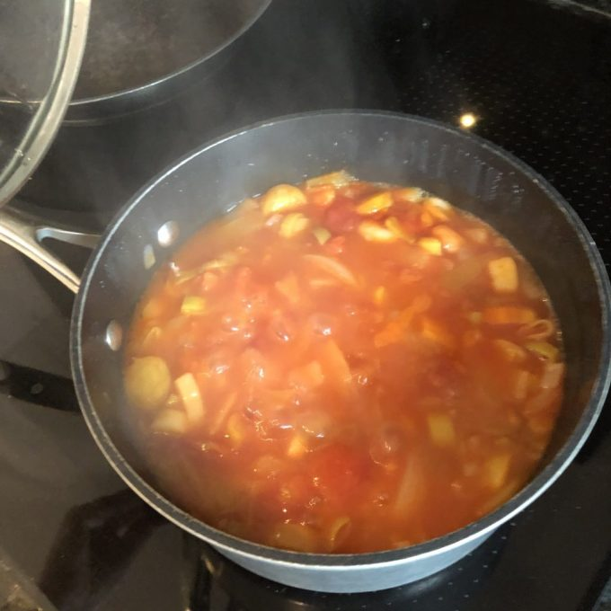 Tamsyn's pan of minestrone soup bubbling on the hob. Steam is rising from the pan.
