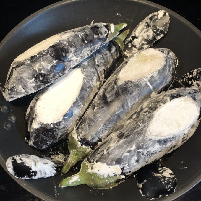 Cornflour coated aubergines in a frying pan. There are too many of them to fit!
