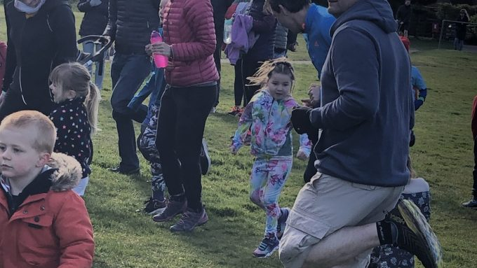 M hopping in a group with others. She is wearing a floral tracksuit and is smiling.