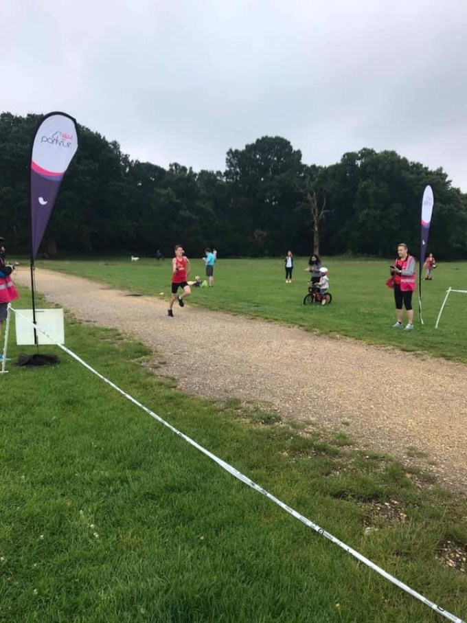 One of the first finishers at Southampton parkrun. A young lad sprinting for the finish line in a red vest and black shorts.