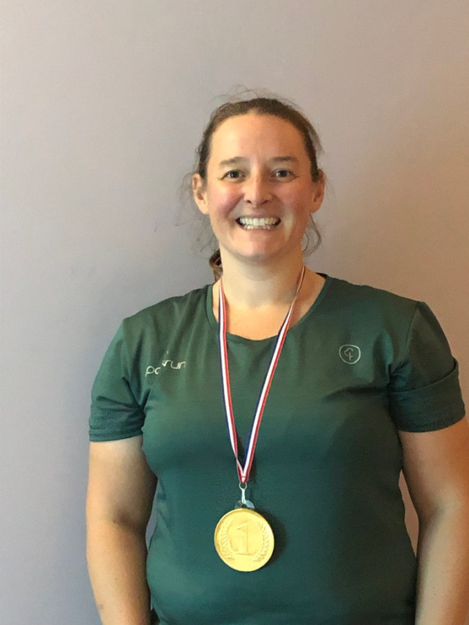 Tamsyn smiling. She is wearing a parkrun t-shirt and a large chocolate medal.