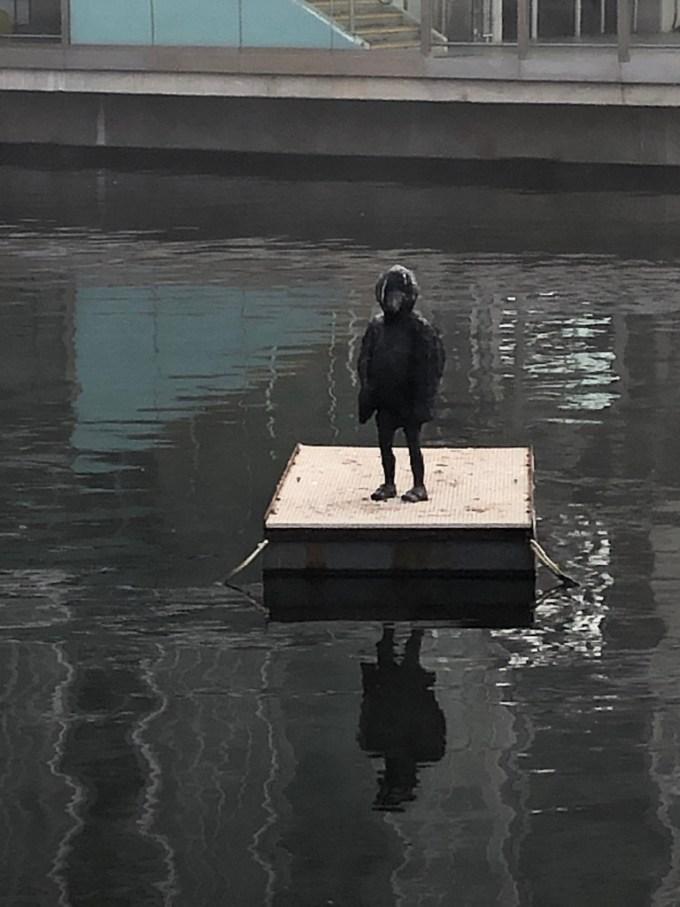 Bird boy statue on the water.