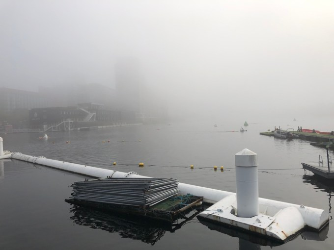 Fog hanging low over the water. Swimmers can just about be seen in the water.