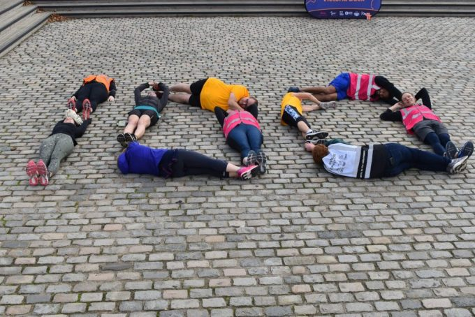 parkrunners and volunteers lying on the floor to spell out 100.