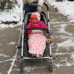 A baby in a Mamas and Papas Urbo on a snowy sidewalk