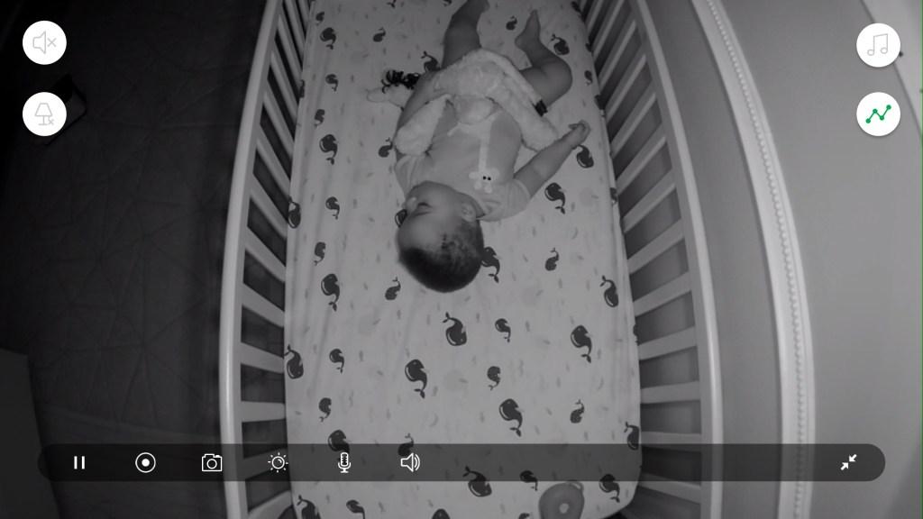 A baby sleeping in a crib shown through Arlo Baby's app