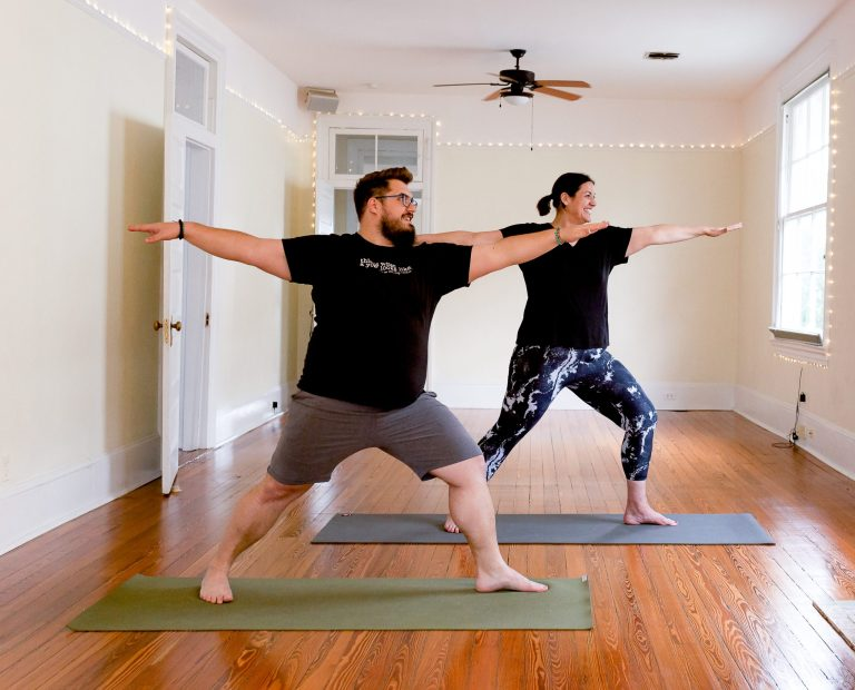 Two individuals standing and practicing Warrior 2